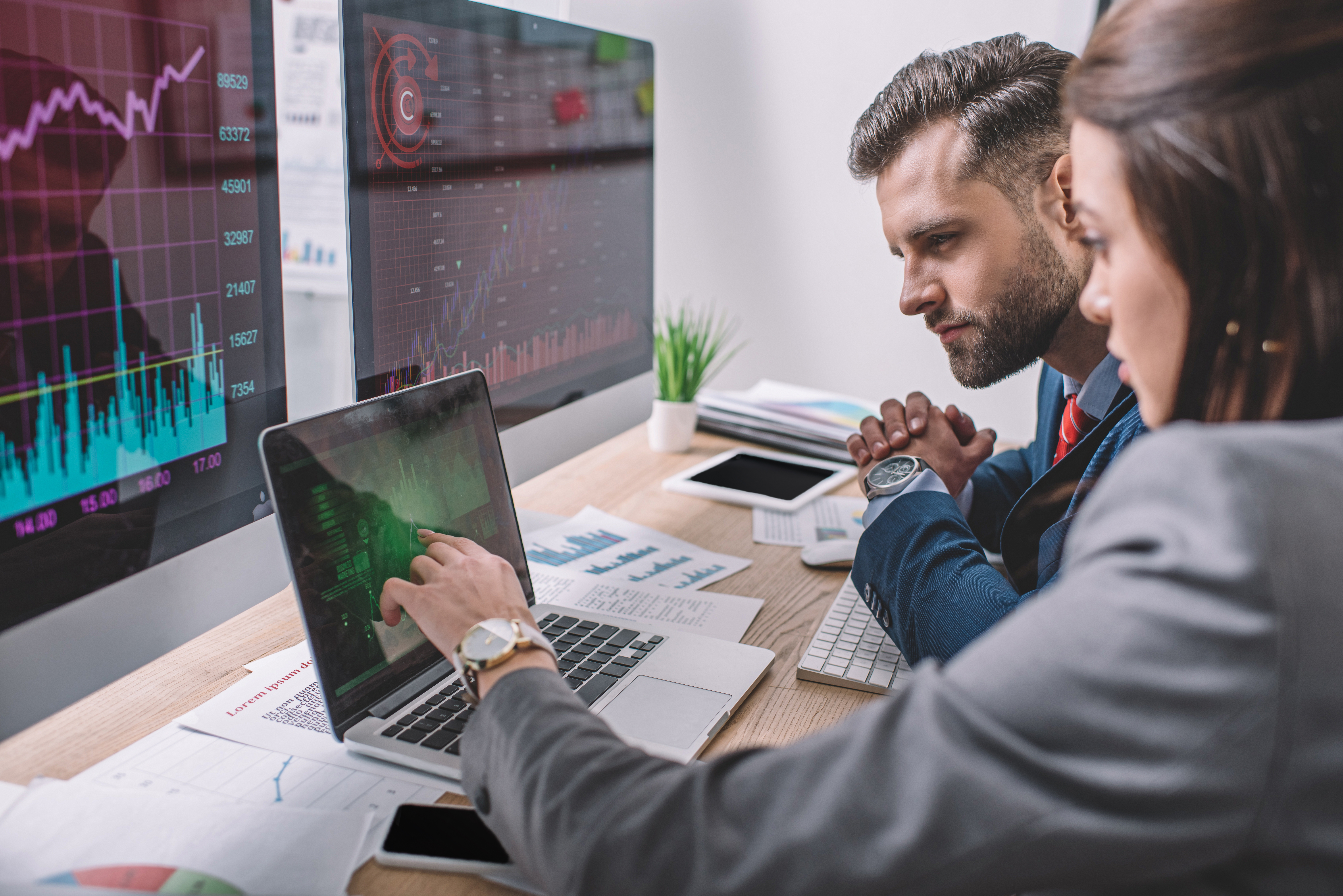Side view of computer systems analysts using charts on computer monitors while working in office